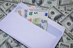 Euro in an envelope. On the background of dollars stock image