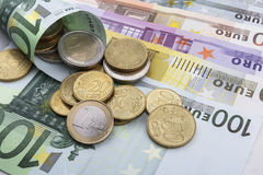 Euro (EUR) coins and notes. Coins on top a 100 EUR note Stock Images