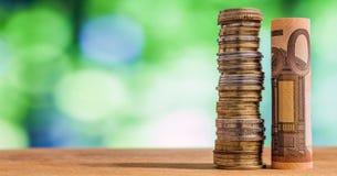Euro fünfzig rollte Rechnungsbanknote, mit Euromünzen auf grünem blurre Stockfotografie