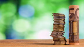 Euro fünfzig rollte Rechnungsbanknote, mit Euromünzen auf grünem blurre Stockbild