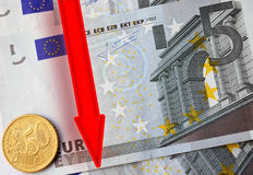 Euro Falls. Red Arrow Decrease Down over Euro Banknotes and Coin Royalty Free Stock Photo