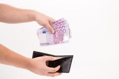 Euro femhundra i handväska och hand Arkivfoton