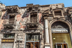 Euro and Financial crisis hits southern Europe hard. PALERMO, SICILY/ITALY - JUNE 26 2013: Bank of Sicily Banco di Sicilia aside of a rotten building on June 26 Royalty Free Stock Photography