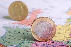 Euro in front of Pound. Euro Coin on Map of Europe and blurred pound coin on Britain. Shows a Eurocentric view of the currencies, with it more dominant than the Royalty Free Stock Image
