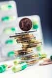 Euro geld en geneesmiddelen Euro muntstukken en pillen Muntstukken op elkaar in verschillende posities en vrij pillen rond worden Stock Foto's