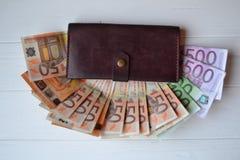 Euro geldbankbiljetten en portefeuille op het witte houten bureau Bedrijfsgeldachtergrond Stock Foto