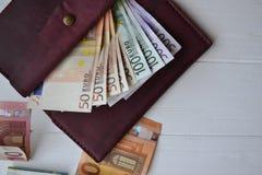 Euro geldbankbiljetten en portefeuille op het witte houten bureau Bedrijfsgeldachtergrond Stock Afbeeldingen