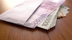 Euro geldbankbiljetten Envelopbankbiljetten op de lijst Corruptiesysteem Euro Geldmunt Het geld van het envelopcontante geld op d stock videobeelden