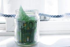 Euro in glass jar. Keeping euro money in glass jar. Glass jar on the windowsill royalty free stock photo