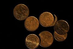 Euro gold coins from above. Euro coins in a pile from above on top of a black background royalty free stock photo