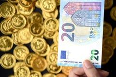 Euro 20 an Hand und Goldmünzen Stockfotografie