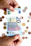 Euro 20 an Hand und Münze Lizenzfreie Stockfotos