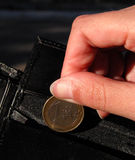 Euro,hand and wallet. Woman fingers inserting a 1euro coin in a man wallet Stock Images