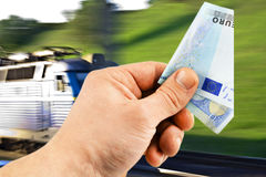 The euro in his hand on a background of train stock photography