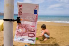 Euro On Holiday. A ten euro bill closeup photograph. Child playing on beach in the background Stock Images
