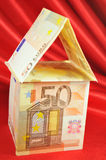 Euro house. House made of euro banknotes on red background Royalty Free Stock Photos