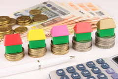 Euro House Money. A rising stack of Euro coins, with toy houses on top. Also cash, calculator and pen. A Euro house financial metaphor Royalty Free Stock Image