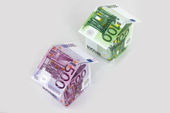 Euro houses. Two colorful houses built of different euro bills. Isolated on a white background Royalty Free Stock Images