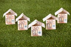 Euro Houses On Grassy Land. Houses made of euro notes on grassy land Royalty Free Stock Image