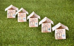 Euro Houses On Grassy Land. Houses made of euro notes on grassy land Stock Photo