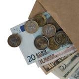 Euro i dolarowi rachunki, euro monety rozpraszali z koperty odosobniony fotografia stock