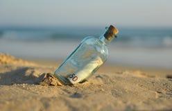 euro 50 i en flaska på stranden Arkivbild