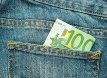 euro 100 i facket av jeans Arkivfoto