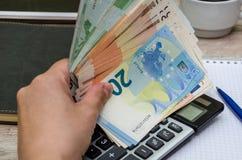 Euro i hand på bakgrunden av en anteckningsbok- och räknemaskinnärbild arkivbilder