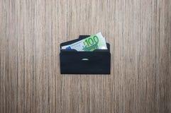 Euro im schwarzen Umschlag auf Holztisch Beschneidungspfad eingeschlossen lizenzfreie stockbilder