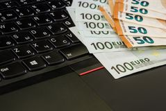 Euro on laptop keyboard close up royalty free stock photography