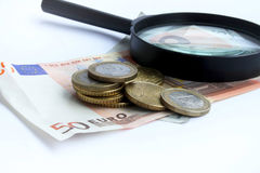 Euro and magnifier. Euro banknotes and coins placed over each other and magnifier stock photo