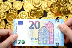 Euro 20 a mano y monedas de oro Fotografía de archivo