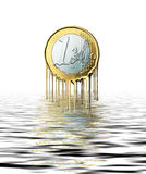 Euro meltdown. One Euro coin with the lower rim melting and dropping into the sea below. A concept image of currency problems in the Euro zone Stock Images