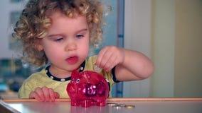 Euro- moedas da inserção bonito da menina no piggybank vídeos de arquivo