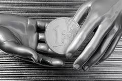 Euro- moedas de prata nas mãos futuristas do robô Imagem de Stock Royalty Free