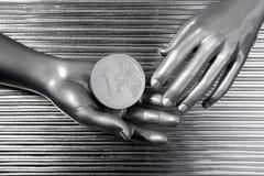 Euro- moedas de prata nas mãos futuristas do robô Foto de Stock