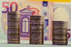Euro- moedas empilhadas contra um euro de papel do valor cinqüênta da denominação Fotos de Stock
