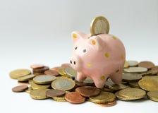 Euro moneta che cade nel porcellino salvadanaio sopra il mucchio della moneta Fotografie Stock Libere da Diritti
