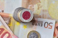 Euro moneta con la bandiera nazionale del Giappone sugli euro precedenti delle banconote dei soldi Fotografie Stock Libere da Diritti