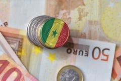 Euro moneta con la bandiera nazionale del Senegal sugli euro precedenti delle banconote dei soldi Fotografia Stock