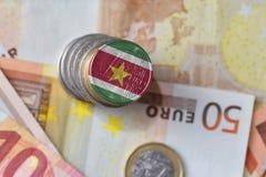 Euro moneta con la bandiera nazionale del Surinam sugli euro precedenti delle banconote dei soldi Fotografia Stock Libera da Diritti