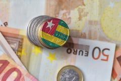 Euro moneta con la bandiera nazionale del Togo sugli euro precedenti delle banconote dei soldi Fotografie Stock