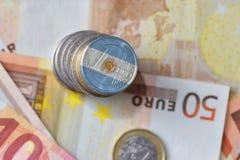 Euro moneta con la bandiera nazionale dell'argentina sugli euro precedenti delle banconote dei soldi Immagini Stock Libere da Diritti