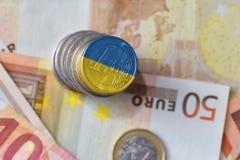Euro moneta con la bandiera nazionale dell'Ucraina sugli euro precedenti delle banconote dei soldi Fotografia Stock Libera da Diritti