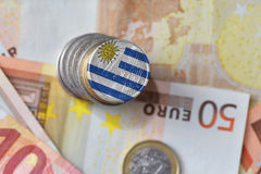 Euro moneta con la bandiera nazionale dell'Uruguai sugli euro precedenti delle banconote dei soldi Immagini Stock