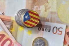 Euro moneta con la bandiera nazionale della Catalogna sugli euro precedenti delle banconote dei soldi Fotografia Stock