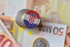 Euro moneta con la bandiera nazionale della Croazia sugli euro precedenti delle banconote dei soldi Immagine Stock