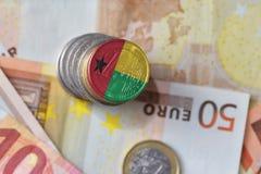 Euro moneta con la bandiera nazionale della Guinea-Bissau sugli euro precedenti delle banconote dei soldi Fotografie Stock Libere da Diritti