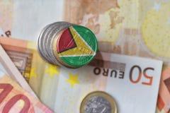 Euro moneta con la bandiera nazionale della Guyana sugli euro precedenti delle banconote dei soldi Fotografia Stock