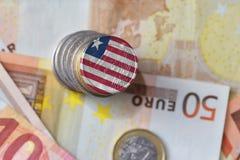 Euro moneta con la bandiera nazionale della Liberia sugli euro precedenti delle banconote dei soldi Fotografia Stock Libera da Diritti